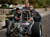 – In the street in front of his Ridgecrest home drag racer and Dust Devils Auto Club member Cecil Wiles pushes his Super Comp dragster with help of...