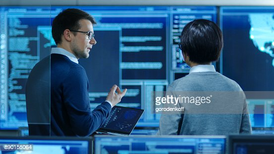 In the System Control Room IT Specialist and Project Engineer Have Discussion while Holding Laptop, they're surrounded by Multiple Monitors with Graphics. They Work in a Data Center on Data Mining, AI and Neural Networking. : Stock Photo