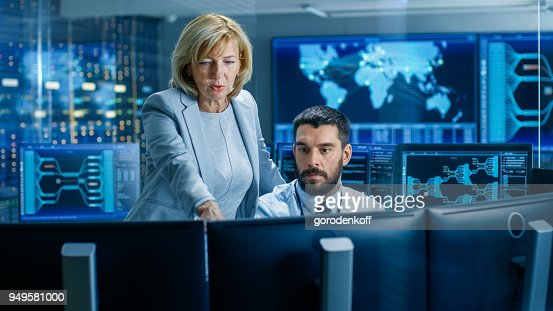 In the System Monitoring Room Senior Supervisor Controls Work of the Operator. They're Surrounded by Monitors Showing Relevant Technical Data. : Stock Photo