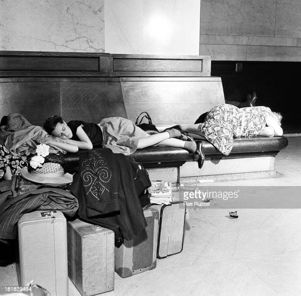 In the waiting room at Grand Central Station a young girl sleeps on a bench as she waits for transportation to a summer camp New York New York 1948