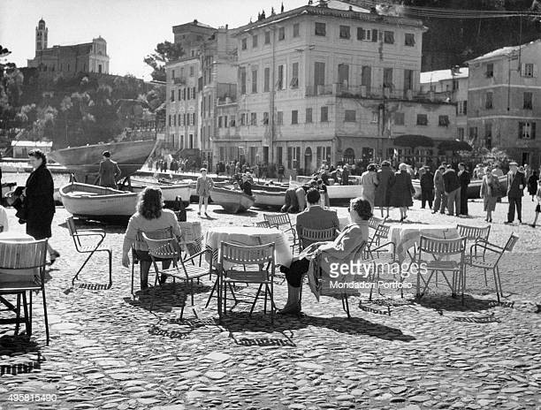 In the wellknown Piazzetta di Portofino a man and two women are sitting at outdoors bar tables in front of them the hamlet and the boats pulled from...