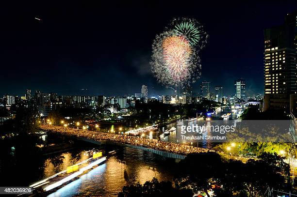 In this aerial and multiple exposure image fireworks explode during the Tenjin Festival along the Okawa River on July 25 2015 in Osaka Japan The...