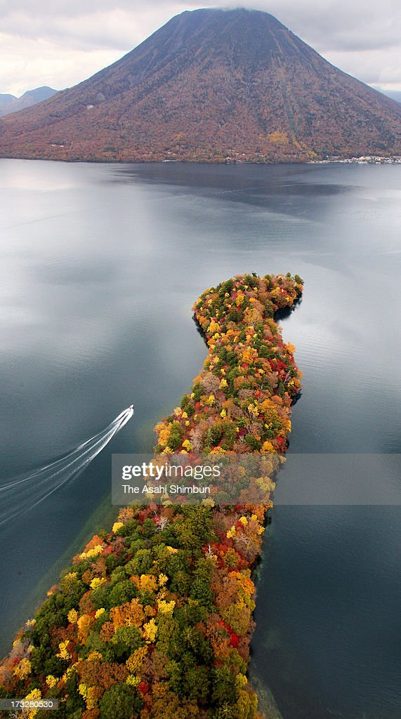 In this aerial image, a boat runs near Hacchodejima that covered by colored leaves at Lake Chuzenji on October 26, 2012 in Nikko, Tochigi, Japan.
