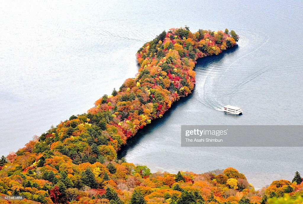 In this aerial image a boat runs near Hacchodejima that covered by colored leaves at Lake Chuzenji on October 19 2011 in Nikko Tochigi Japan