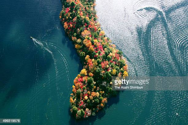 In this aerial image a boat runs near Hacchodejima that covered by colored leaves at Lake Chuzenji on October 28 2007 in Nikko Tochigi Japan