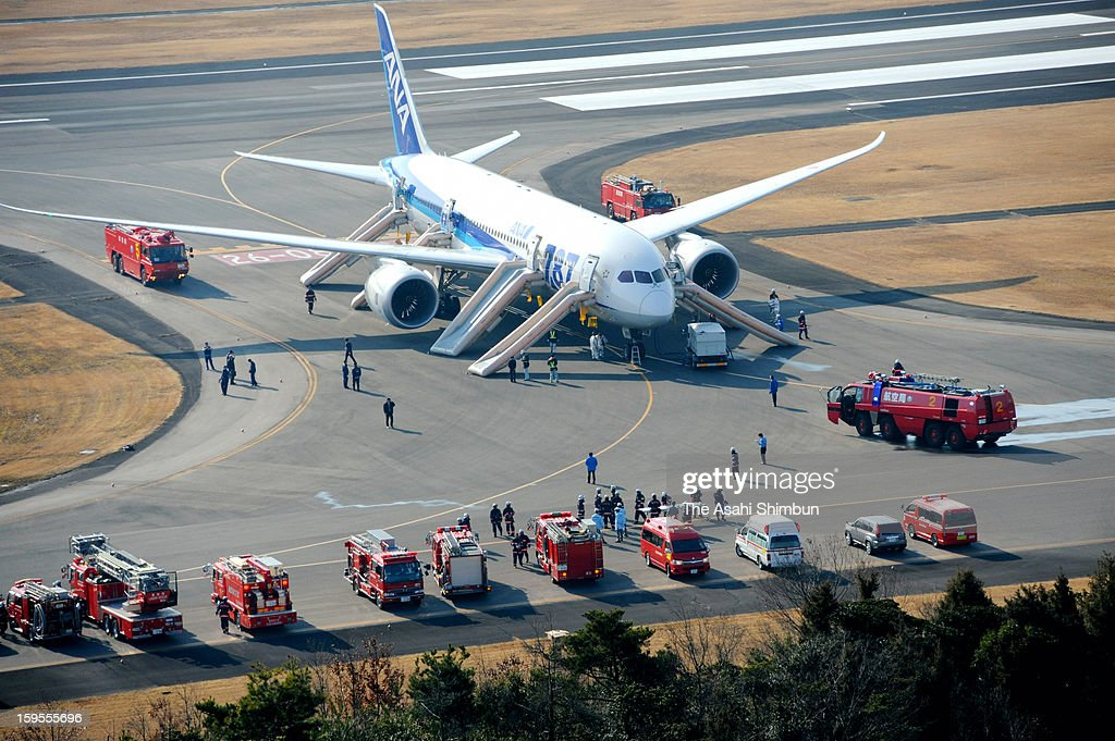 In this aerial image, a Boeing 787 airplane is seen while firefighters are on stand-by at the runway of Takamatsu Airport on January 16, 2013 in Takamatsu, Kagawa, Japan. All Nippon Airways flight 692, departing from Yamaguchi Ube airport at 8:10 detected smoke inside the aircraft, made an emergency landing at Takamatsu Airport on 8:45, all 137 passengers and crews evacuated from the plane.