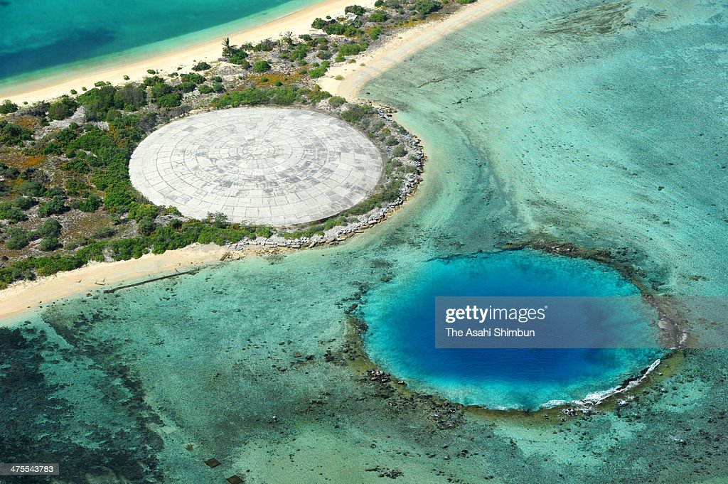 In this aerial image, a creater covered by concrete to keep decontaminated soil (L) and another creater both created by nuclear testings are seen on January 29, 2014 in Enewetak Atoll, Marshall Islands. The United States conducted 67 tests of nuclear weapons in the Marshall Islands, the site of the U.S. Pacific Proving Grounds, between 1946 and 1958. In 1977, radioactive strontium-90 exceeding U.S. environmental standards was detected in well water. The following year, the U.S. Interior Department said cesium-137 levels on the atoll were so high that residents could not permanently live there. That forced the islanders to once again leave the atoll. With the 60th anniversary of the hydrogen bomb test approaching, there is still no indication of when the former residents can return.