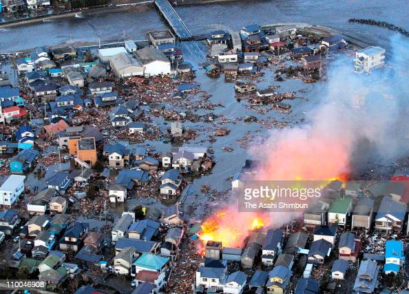 In this aerial image a fire caused by tsunami is seen in the flooding Iwaki City after a 90 magnitude strong earthquake struck off the coast of...