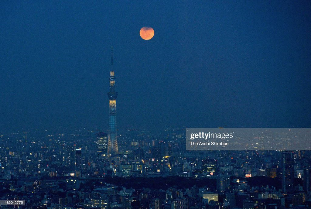 In this aerial image, a full moon with its top eclipsed rises alongside Tokyo Skytree on April 15, 2014 in Tokyo, Japan. A 'blood moon' was seen rising in the evening sky across eastern Japan.