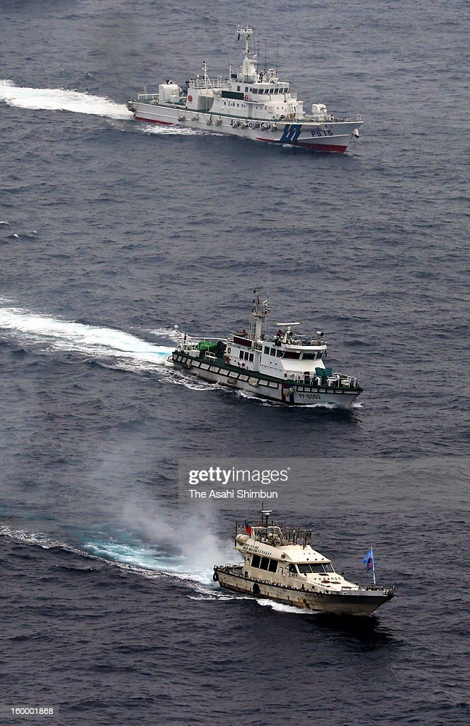 In this aerial image, a Taiwanese boat (bottom) sails along a Taiwanese Coast Guard vessel (middle) and a Japan Coast Guard (JCG) patrol ships (top) at some 33 kilometers west-southwest from Uotsuri Island on January 24, 2013 in Ishigaki, Okinawa, Japan. The boat, protected by four Taiwanese coast guard vessels, enters the contiguous zone of disputed islands known as Senkaku Islands in Japan and Diaoyu Islands in China, Tiaoyutai in Taiwan.