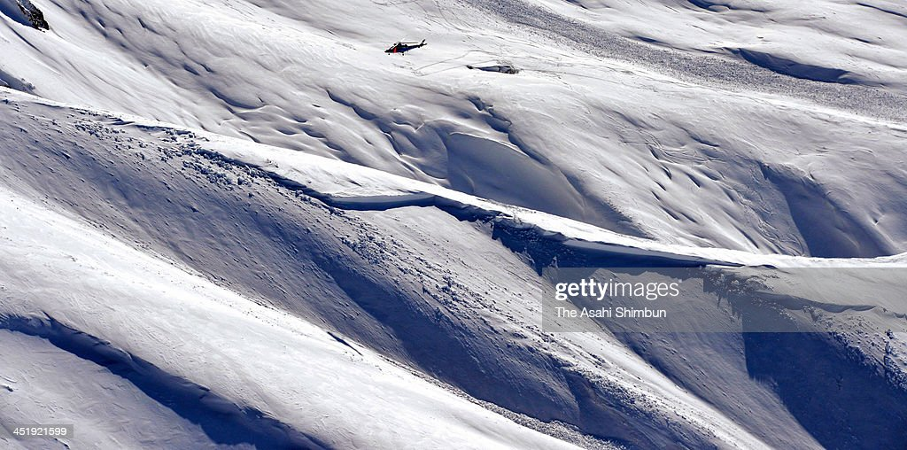 In this aerial image, a Toyama prefecture police helicopter is in searching operation above a snow avalanche site at Mt. Masago of the Tateyama Mountains on November 24, 2013 in Tateyama, Toyama, Japan. All seven people involved in the avalanche confirmed dead.
