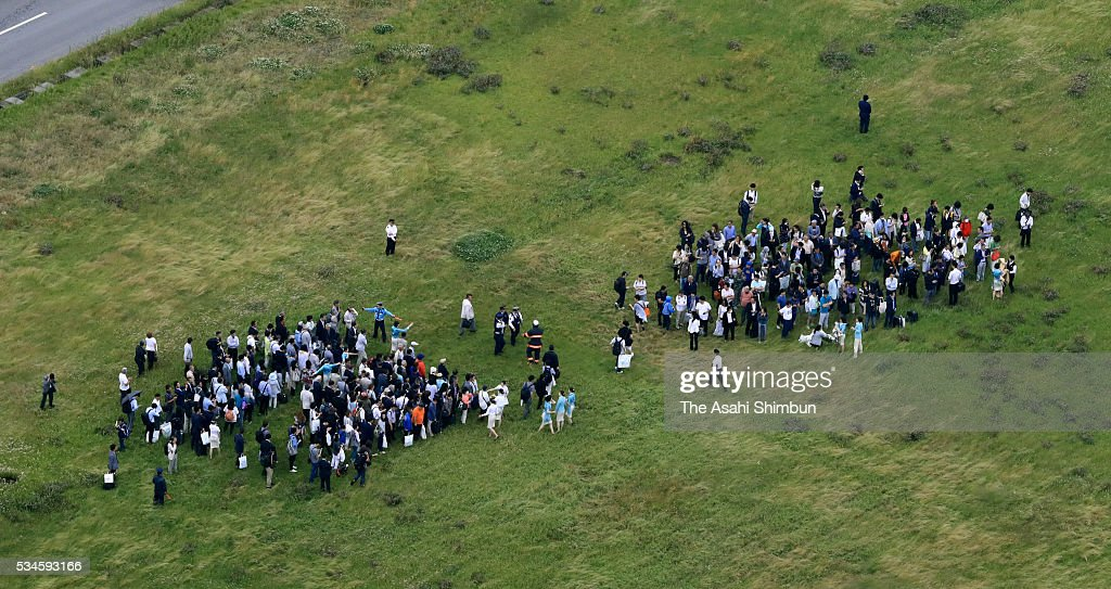 In this aerial image, Evacuated passengers and crews are seen next to the runway after the fire of the Korean Air 2708 bound for Seoul at the Haneda International Airport on May 27, 2016 in Tokyo, Japan. 319 passengers and crews have safely evacuated. C runway has been closed.