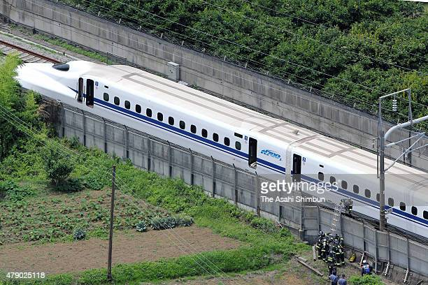 In this aerial image fire fighters are seen approaching the Shinkansen bullet train 'Nozomi 225' halted on track to extinguish a fire inside on June...