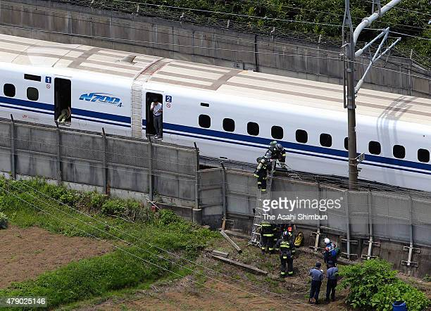 In this aerial image fire fighters are seen entering the track to extinguish the fire in the Shinkansen bullet train 'Nozomi 225' halted on track on...
