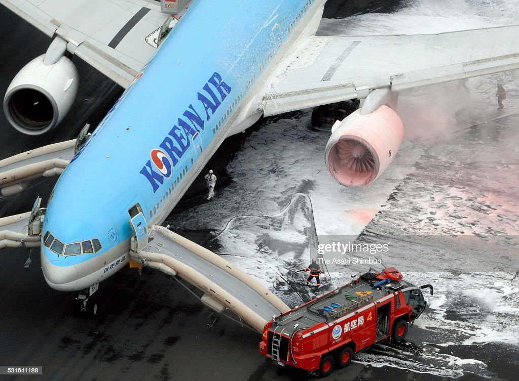 In this aerial image, fire fighters spray foam to an engine on the left side of the Korean Air 2708 bound for Seoul at the Haneda International Airport on May 27, 2016 in Tokyo, Japan. 319 passengers and crews have safely evacuated. C runway has been closed.