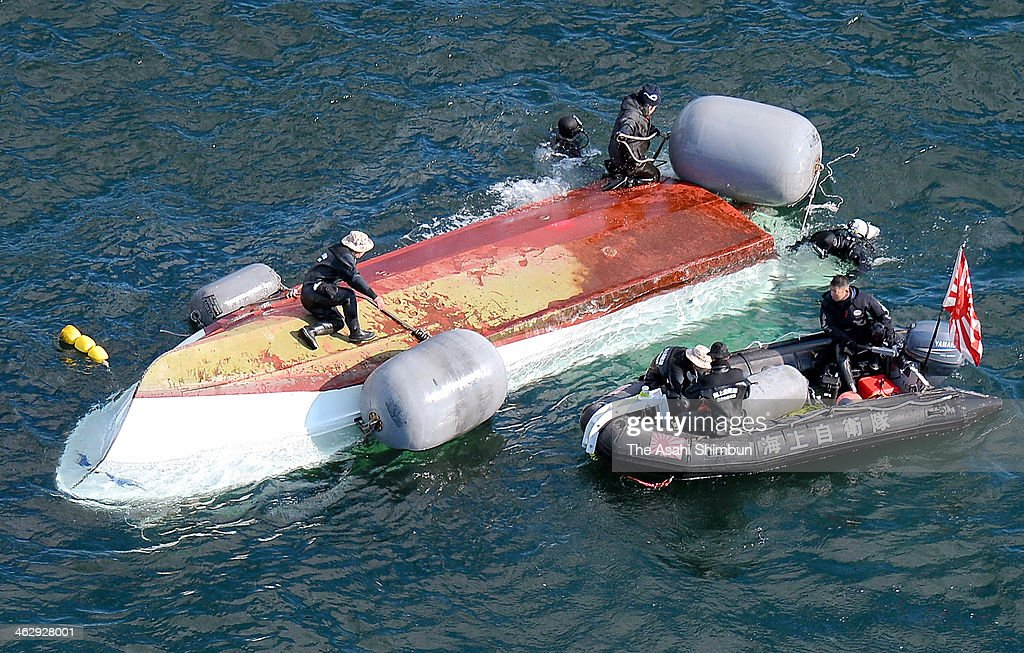In this aerial image, Japan Coast Guard members investigate the cause of the collision with Japan Maritime Self-Defense Force vessel 'Osumi' around the overturned fish boat on January 15, 2014 in Otake, Hiroshima, Japan. Two among the four people on the fish boat are reported dead.