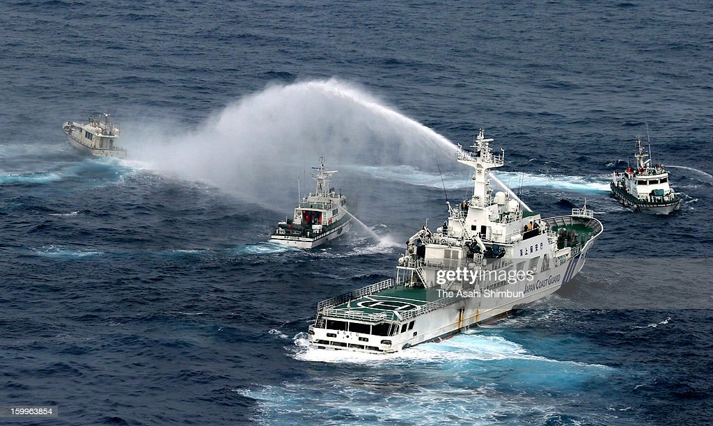 In this aerial image, Japan Coast Guard (JCG) patrol ship (bottom R) fires a water cannon towards a Taiwanese boat (top L) while a Taiwanese coast guard vessel (C) responds at some 33 kilometers west-southwest from Uotsuri Island on January 24, 2013 in Ishigaki, Okinawa, Japan. The boat, protected by four Taiwanese coast guard vessels, enters the contiguous zone of disputed islands known as Senkaku Islands in Japan and Diaoyu Islands in China, Tiaoyutai in Taiwan.