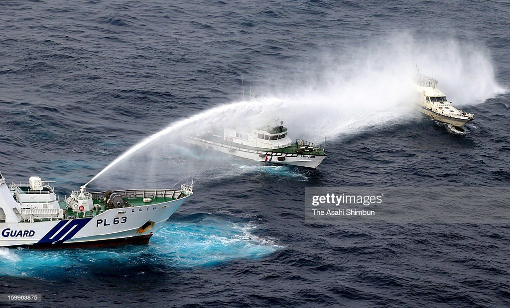In this aerial image, Japan Coast Guard (JCG) patrol ship (L) fires water cannon towards a Taiwanese boat (R) while a Taiwanese coast guard vessel (C) responds at some 33 kilometers west-southwest from Uotsuri Island on January 24, 2013 in Ishigaki, Okinawa, Japan. The boat, protected by four Taiwanese coast guard vessels, enters the contiguous zone of disputed islands known as Senkaku Islands in Japan and Diaoyu Islands in China, Tiaoyutai in Taiwan.