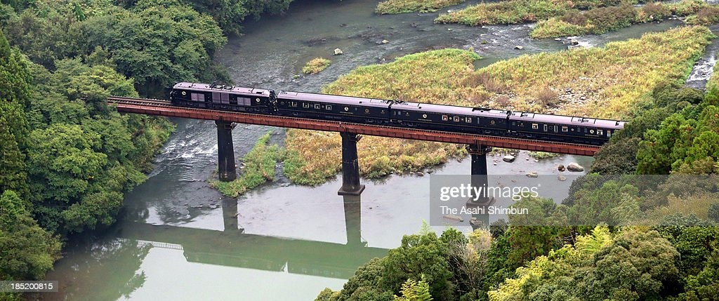 In this aerial image JR Kyushu's luxury sleeper train 'Nanatsuboshi ' crosses an iron bridge on October 15 2013 in Hita Oita Japan When shared by two...