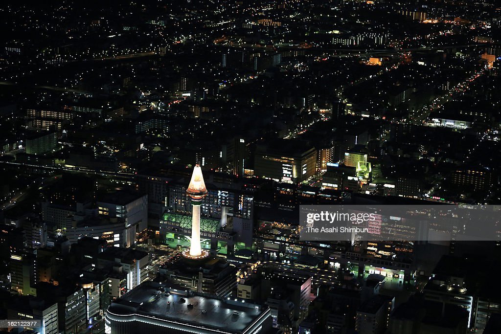 In this aerial image, Kyoto Tower is illuminated on February 17, 2013 in Kyoto, Japan. The net to avoid the paint sprinkling create the candle-look illumination.