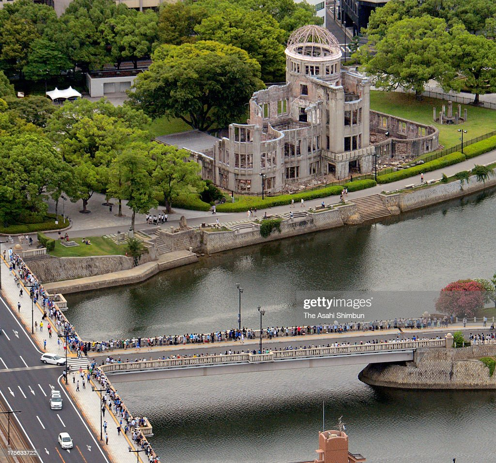 In this aerial image, People look up the sky at 8:15am, from Aioi Bridge, epicenter of the Hiroshima Atomic Bomb, to commemorate 68th anniverasary of the Hiroshima Atomic Bomb on August 4, 2013 in Hiroshima, Japan. The bomb exploded on August 6, 1945.