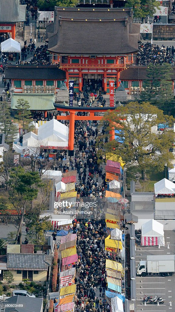 In this aerial image, people walk the main approach to pay their first visit of the year to Fushimi Inari Taisha Shrine on January 2, 2014 in Kyoto, Japan.