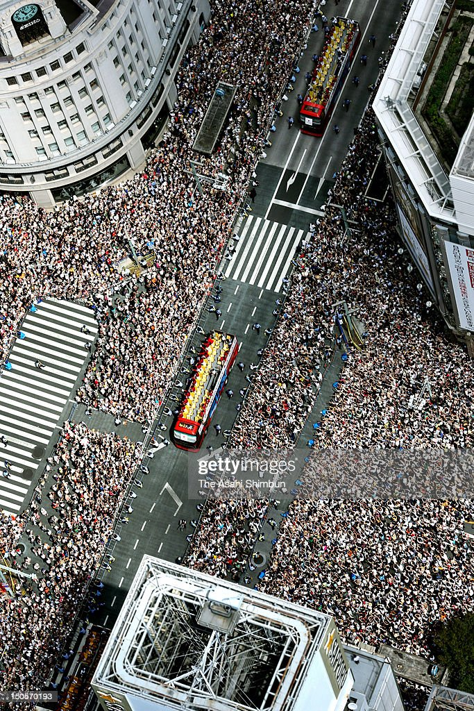 In this aerial image, people wave hands to Japanfs Olympic medalists as their buses parade on the streets of Tokyoes upmarket Ginza district on August 20, 2012 in Tokyo, Japan. An estimated 500,000 people gathered to see the 38 medal winners.