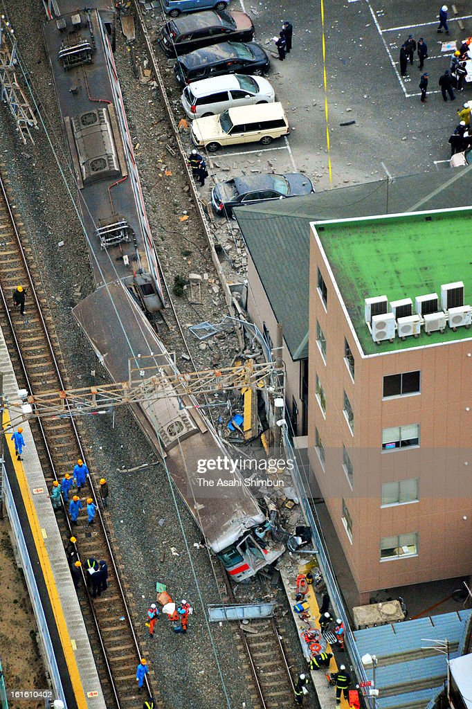In this aerial image, police officers investigate the accident site that Sanyo Electric Railway Co. train and a truck collided near Arai Station on February 12, 2013 in Takasago, Hyogo, Japan. Fifteen people injured by the accident.