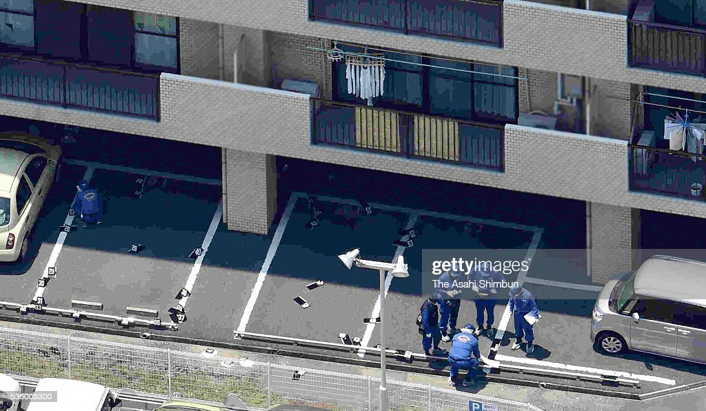 In this aerial image, police officers investigate the parking lot of a condominium where Tadashi Takagi, 55, was found shot several times in the chest and stomach on May 31, 2016 in Okayama, Japan. Takagi is the second-in-command of the Ikeda-gumi organized crime syndicate, which is affiliated with the Kobe Yamaguchi-gumi. The Kobe Yamaguchi-gumi broke away from Japan's largest yakuza organization Yamaguchi-gumi at the end of August 2015.