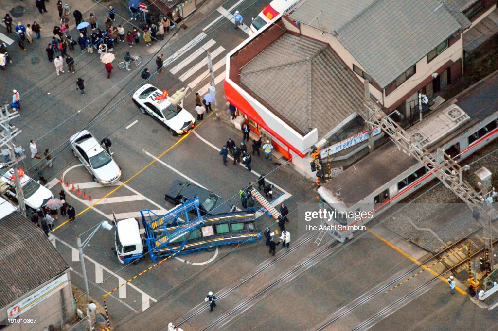 In this aerial image, police officers investigate the railroad crossing that Sanyo Electric Railway Co. train and a truck collided near Arai Station on February 12, 2013 in Takasago, Hyogo, Japan. Fifteen people injured by the accident.