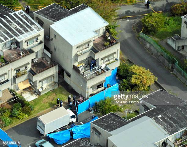 In this aerial image police officers search the area around the burnedout apartment room in a prefecturerun apartment complex on October 6 2017 in...