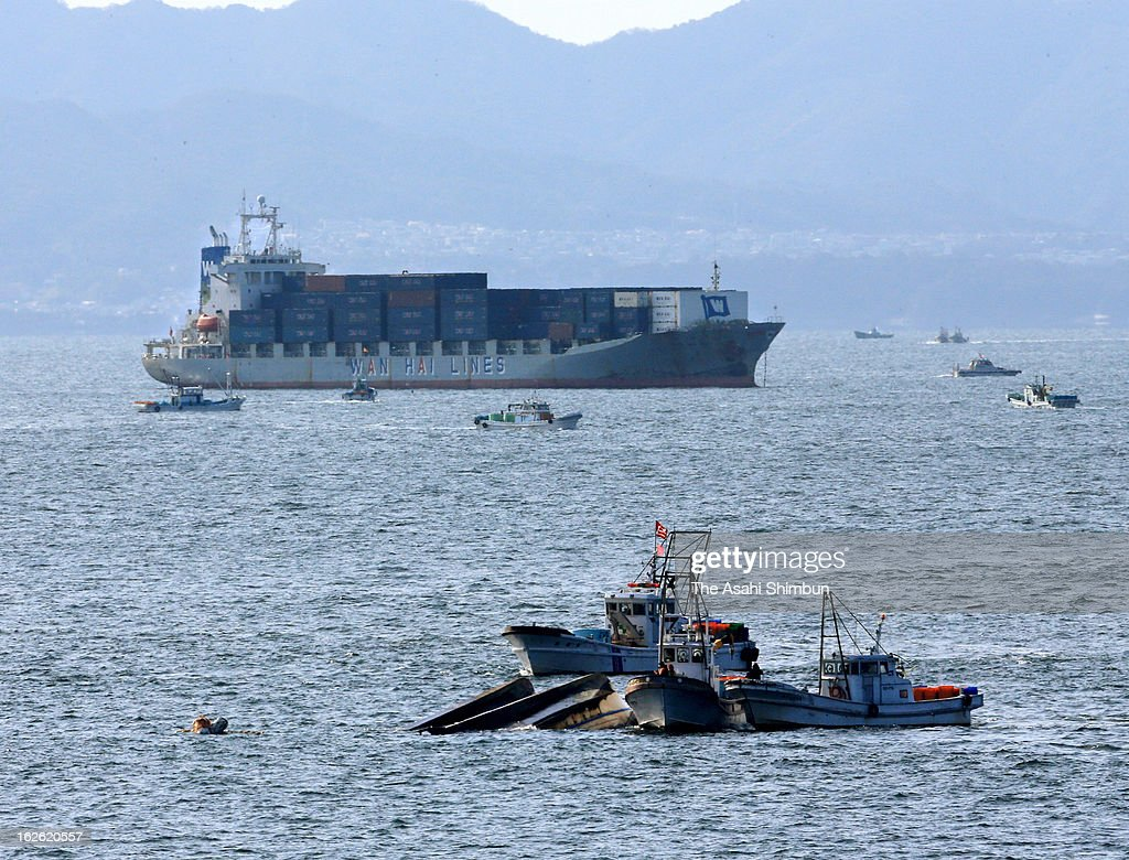 In this aerial image, rescue divers investigate the overturned boats after collision with Taiwanese container vessel 'WAN HAI 162' on February 25, 2013 in Osaka, Japan. Four fishermen were thrown into the sea, one confirmed dead and one is still missing.