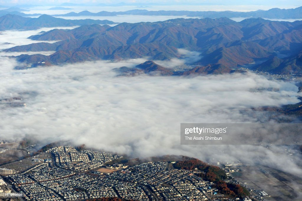 In this aerial image, Sanda city is covered by the sea of cloud on November 28, 2012 in Sanda, Hyogo, Japan.