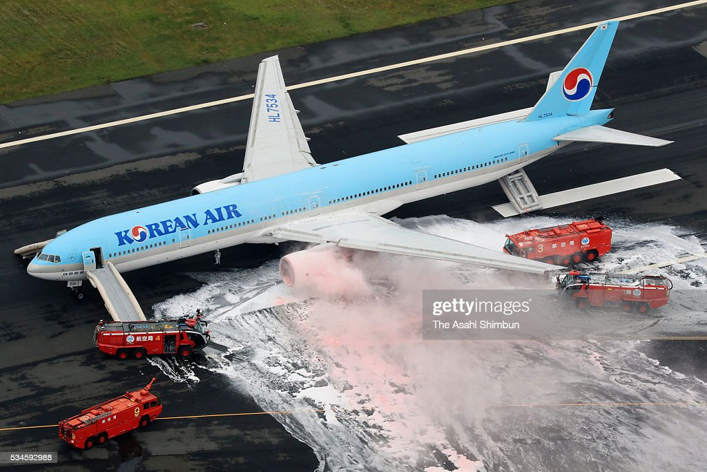 In this aerial image, smoke rise from and engine while fire fighters spray foam on the Korean Air 2708 bound for Seoul at the Haneda International Airport on May 27, 2016 in Tokyo, Japan. 319 passengers and crews have safely evacuated. C runway has been closed.