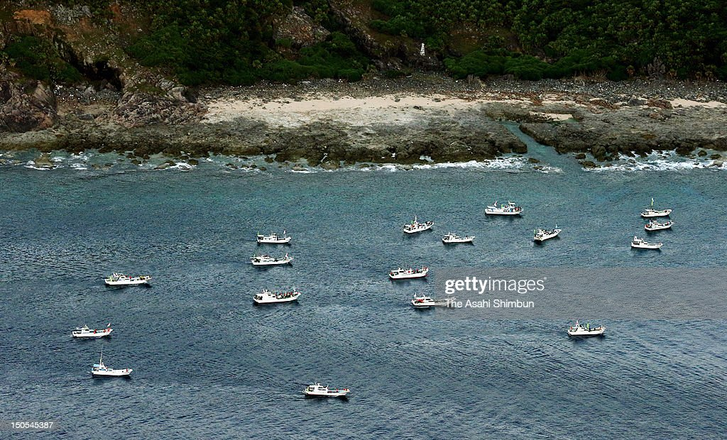 In this aerial image the boats carrying Japanese local assembly members approach to Uotsurijima one of the disputed Senkaku or Diaoyu Islands...