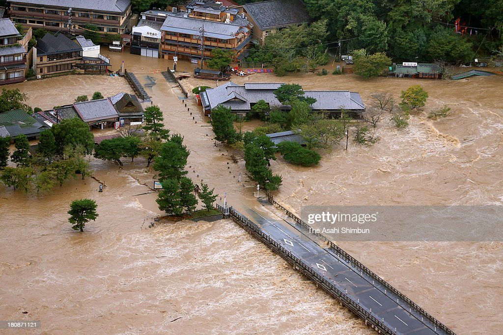 In this aerial image, Togetsukyo Bridge is under flooded Katsuragawa River triggered by typhoon Man-Yi approaching on September 16, 2013 in Kyoto, Japan. The storm hit land near Toyohashi, Aichi Prefecture, before 8 a.m. and moved along Honshu throughout the day, damaging buildings, disrupting transportation and causing blackouts, three killed and five missing.
