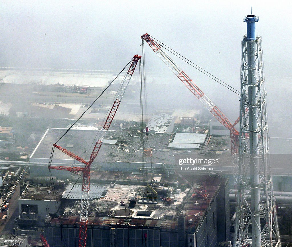 In this aerial image two cranes are used to remove a huge piece of debris from the nuclear fuel storage pool of the No 3 reactor building at the...