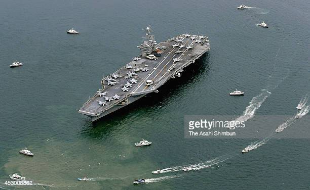 In this aerial image USS Goerge Washington cruises toward Sasabo port while small boats protesting the visit surround the ship on August 1 2014 in...
