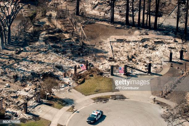 In this aerial view a police officer drives near burned properties in Santa Rosa California on October 12 2017 Hundreds of people are still missing...
