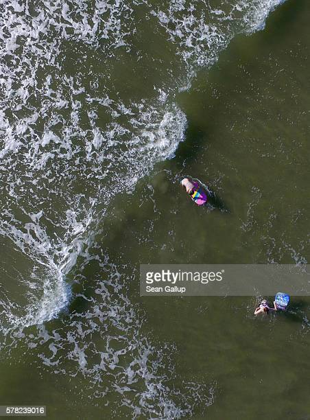 In this aerial view children play in the surf among incoming waves at the beach on July 18 2016 at SanktPeterOrding Germany SanktPeterOrding is among...