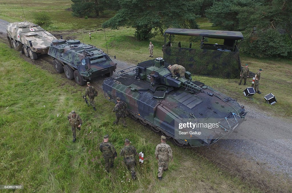 In this aerial view members of the Bundeswehr, the German armed forces, stand next to a Puma infantry fighting vehicle (R) following a demonstration of capabilities of Panzergranadierbataillon 33 of the 1st Panzer Division (1. Panzerdivision) on June 29, 2016 near Neustadt am Ruebenberge, Germany. The Bundeswehr is aquirung the Puma in phases and the vehicle replaces the Marder.