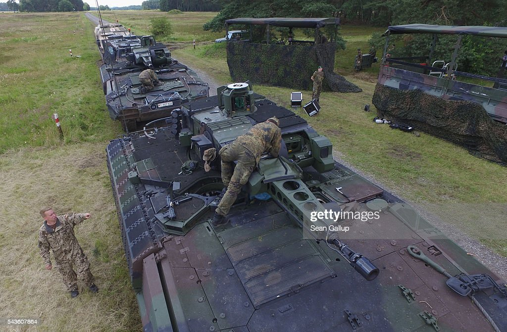 In this aerial view members of the Bundeswehr, the German armed forces, stand at two Puma infantry fighting vehicles following a demonstration of capabilities of Panzergranadierbataillon 33 of the 1st Panzer Division (1. Panzerdivision) on June 29, 2016 near Neustadt am Ruebenberge, Germany. The Bundeswehr is aquirung the Puma in phases and the vehicle replaces the Marder.