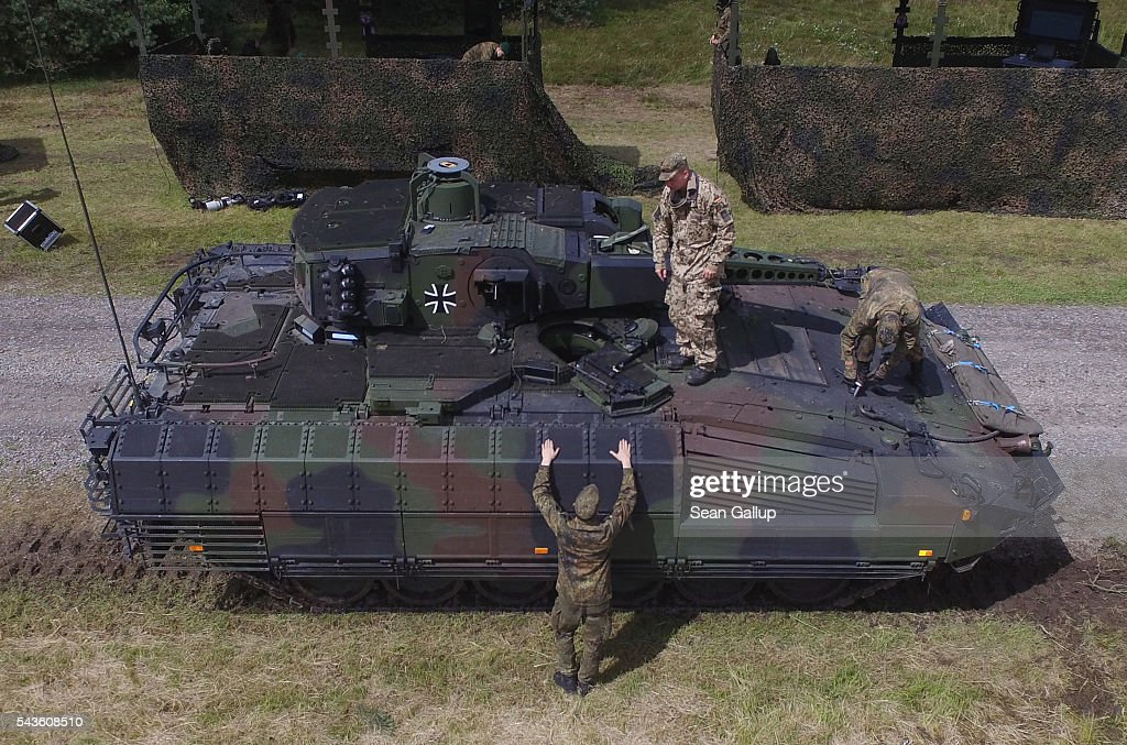In this aerial view members of the Bundeswehr, the German armed forces, step down from a Puma infantry fighting vehicle following a demonstration of capabilities of Panzergranadierbataillon 33 of the 1st Panzer Division (1. Panzerdivision) on June 29, 2016 near Neustadt am Ruebenberge, Germany. The Bundeswehr is aquirung the Puma in phases and the vehicle replaces the Marder.