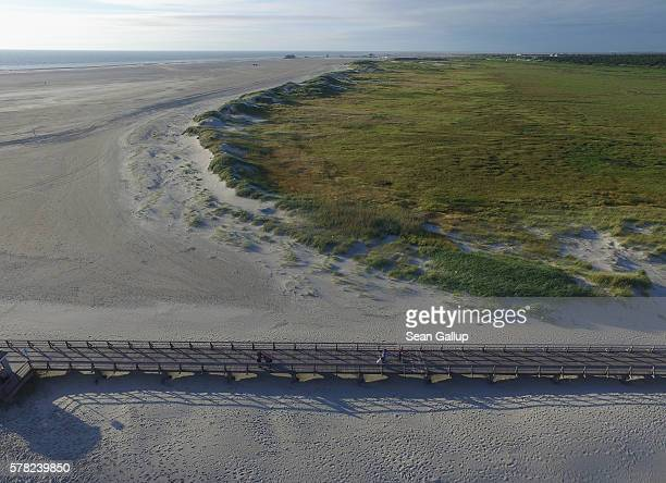 In this aerial view people walk on a wooden walkway near protected dunes and salt marshes at the beach on July 18 2016 at SanktPeterOrding Germany...