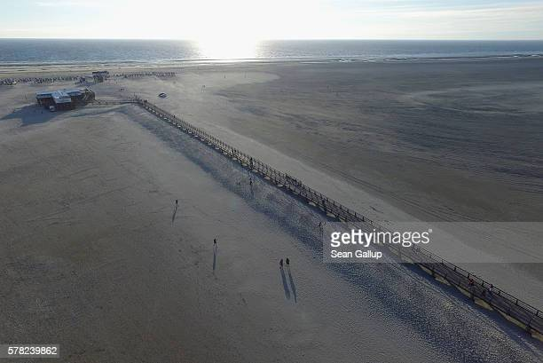 In this aerial view people walk on a wooden walkway on the beach on July 18 2016 at SanktPeterOrding Germany SanktPeterOrding is among the top...