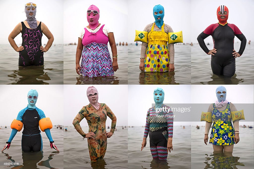 In this composite image Chinese women pose in facekinis in the Yellow Sea on August 21 2014 in Qingdao China The locally designed mask is worn by...