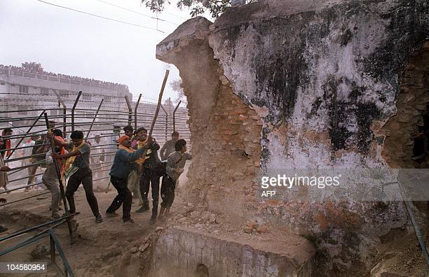 In this December 6 1992 photograph Indian Hindu fundamentalists attack the wall of the 16th century Babri Masjid Mosque with iron rods at a disputed...