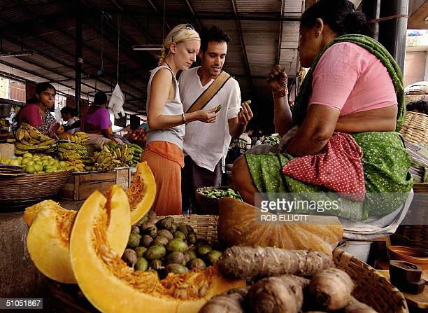 In this file photo taken 01 December 2003 A tourist couple from Israel chat with a local vendor as they check out the fruit at the local market in...
