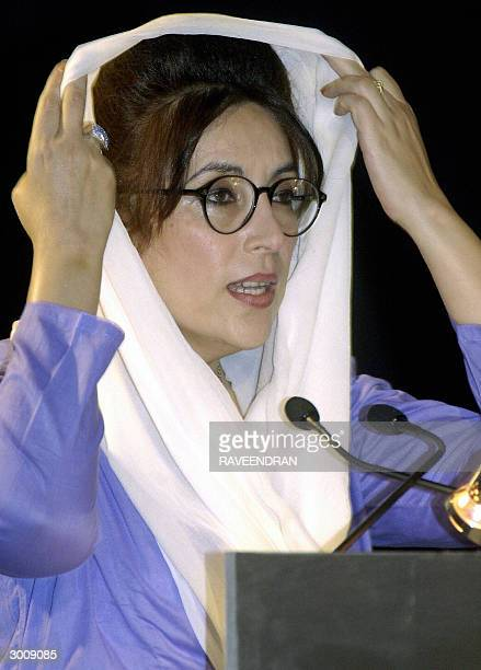 In this file photo taken 13 December 2003 former Pakistani Prime Minister Benazir Bhutto adjusts her headscarf as she addresses a conference entitled...