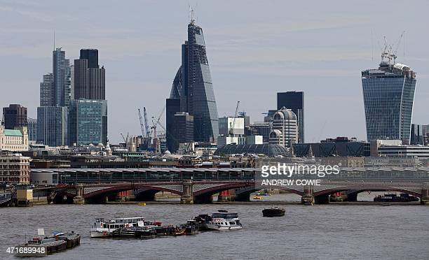 In this file photograph taken on August 7 2013 in London England boats sit moored on the River Thames as the City Of London stands on the horizon...